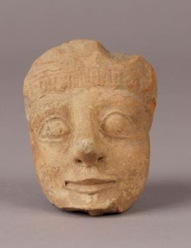 Head of a male figure with incised traces of a headdress