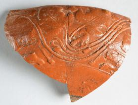 Fragment of a Samian ware bowl with scrolling tendrils and leaves
