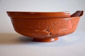 Fragmentary Samian ware bowl with scrolling vine and leaf motifs