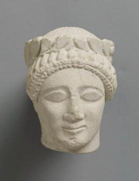 Head of a fragmentary male votive figure wearing a wreath