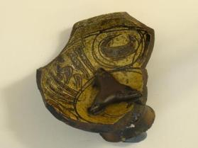 Slip-incised ware vessel fragment (sherd) with attached trivet