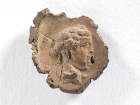 Impression of a seal bearing the head of Dionysus crowned with ivy