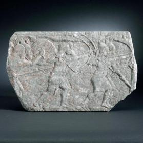 Relief sculpture of archers attacking a city