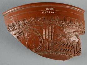 Fragment of a Samian ware bowl featuring scenes of a running hound and winged figure