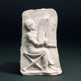 Plaque with harp-player