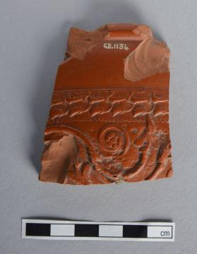 Fragment of a Samian ware bowl with spiraling tendril scroll motif