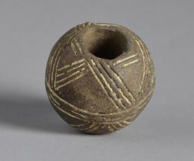 Spindle whorl of Black Polished ware with incised decoration