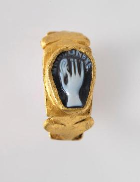 Ring inset with cameo depicting a hand pinching an earlobe