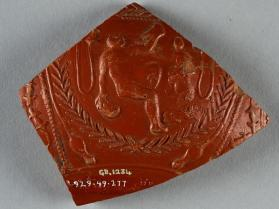 Fragment of a Samian ware bowl with seated nude male figure