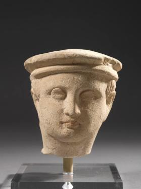 Head of a young male figure wearing a flat cap or kausia