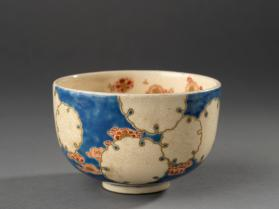 Tea bowl with design of flowers on blue background