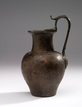 Jug with mask on handle