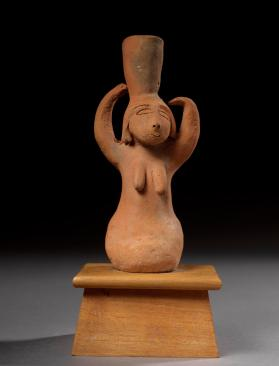 Kneeling female figure with pot on head
