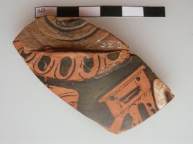 Fragment of the lid of an Attic vessel, decorated in red figure technique with a woman (just the top of her head) holding a jewellery box.