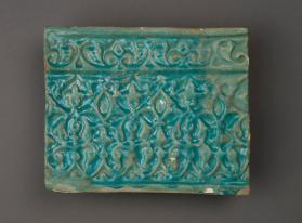 Monochrome relief tile with arabesques from an architectural frieze