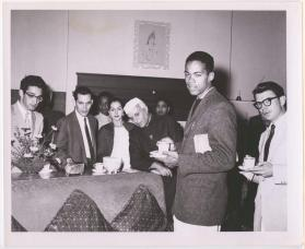 Guests having tea with Prime Minister Jawaharlal Nehru at a USIS (India) event