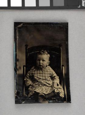 [Very young boy seated, w/top curls, in plaid dress and striped socks]