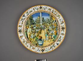 "Large Dish (bascile) (bassin) depicting 'A Banquet in a Piazza' from ""The Life of Julius Caesar."" Possibly from the ""Spanish Service"", commissioned by the Duke of Urbino (Guidobaldo II della Rovere (1514–1574) as a gift to the King Philip II (1527-1598) of Spain to commemorate the marriage of the duke's daughter Virginia della Rovere (1544-1571) to Federico Borromeo, the Duke of Camerino (1535-1562)"