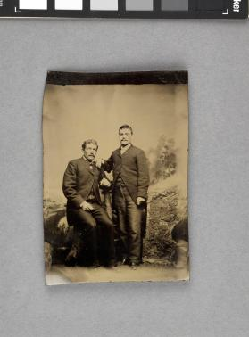 [Two men with moustaches, one seated, by boulder prop]