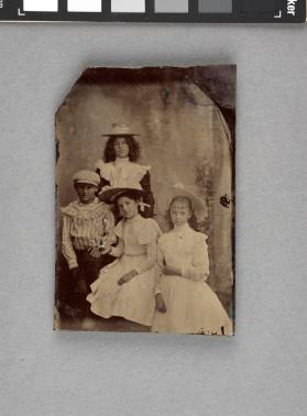[Four youths, boy in cap, girls wearing hats, two of girls in white dresses]