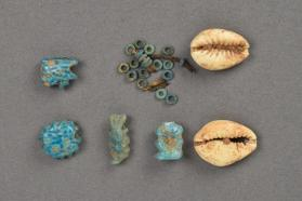 Amulets (wadjet eyes and Bes) and beads (disc and cowrie shell)