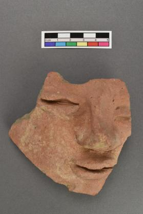 Clay face from vessel or miniature coffin