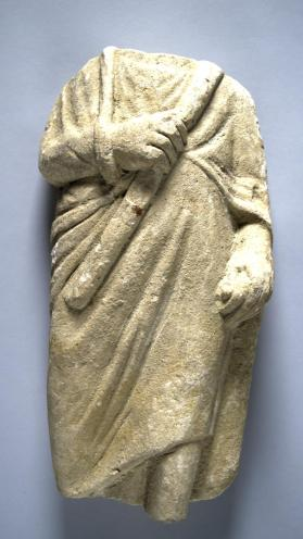 Fragmentary male votive figure wearing long himation
