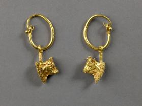 Pair of gold hoop earrings with bulls' head pendants