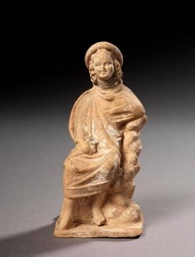 """Tanagra"" type figure of a seated boy"