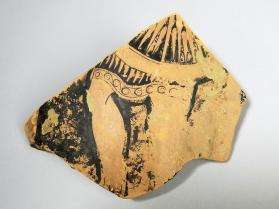Red-figure vessel fragment depicting legs of a warrior carrying a shield