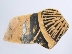 Red-figure vessel fragment with part of a draped figure and a shield