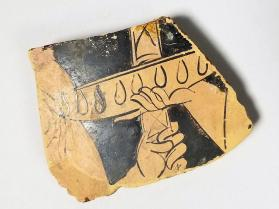 Red-figure vessel fragment with a hand holding an offering dish