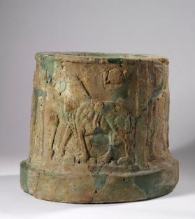 Hollow cylinder decorated with rams and a lion