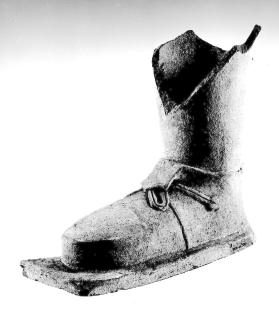 Foot and part of leg of votive figure, wearing a shoe