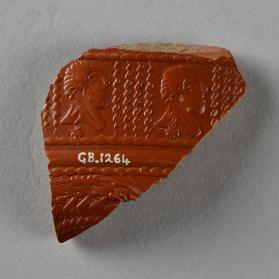 Fragment of a Samian ware bowl with bearded male busts