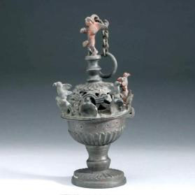 Censer with domed lid, surrounded by birds and crosses, with Cupid-like finial