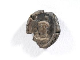 Impression from a seal with a frontal bust of Athena wearing a crested helmet