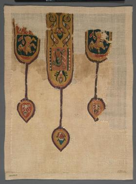 Pendant ornaments from the neck of a tunic