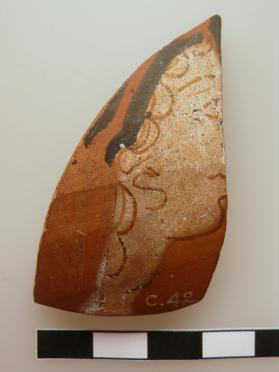 Fragment from the body of an Attic thick-walled vessel, probably a krater, decorated in red figure technique with the head of a woman.